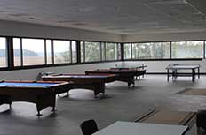 A row of old pool tables in an empty room.