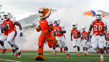 The Savannah State University Football team makes a dramatic entrance through a cloud smoke.