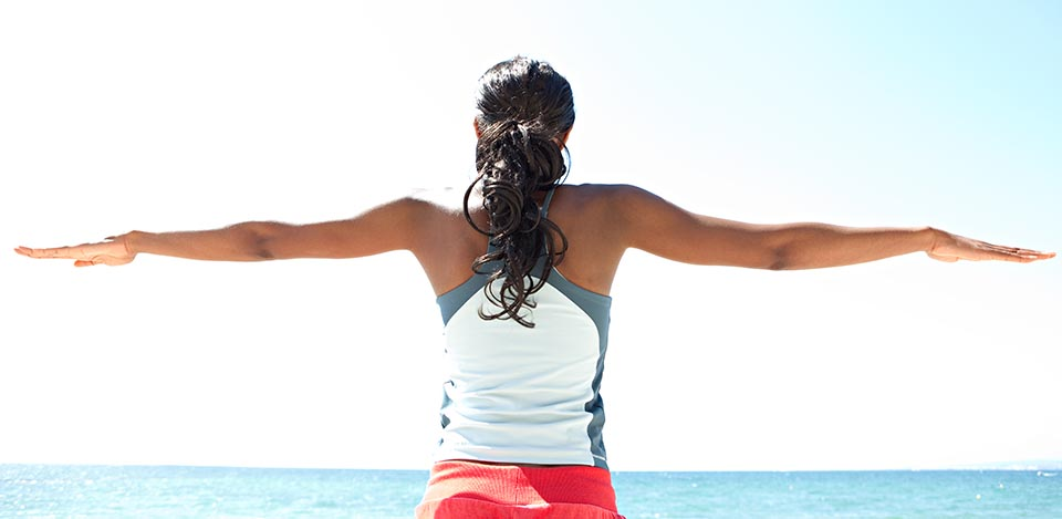 Backview of a woman wearing fitness clothing on a beach with outstretched arms
